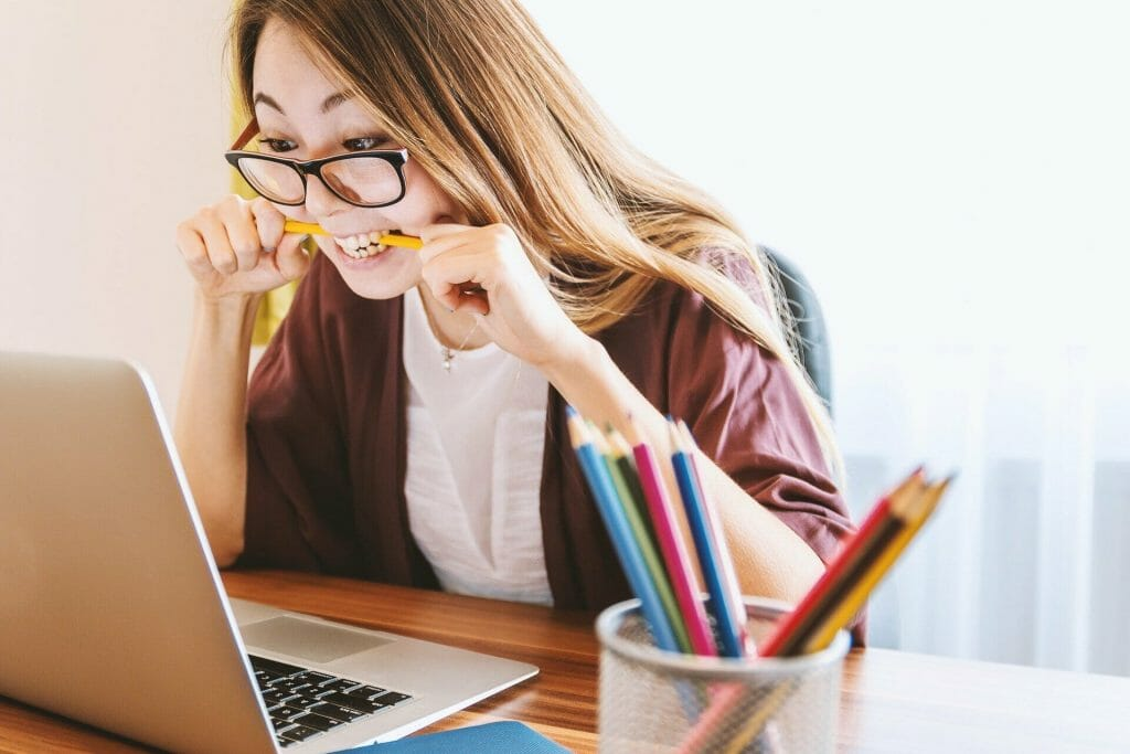 How to start studying and stop procrastinating - student chewing pencil while looking at laptop