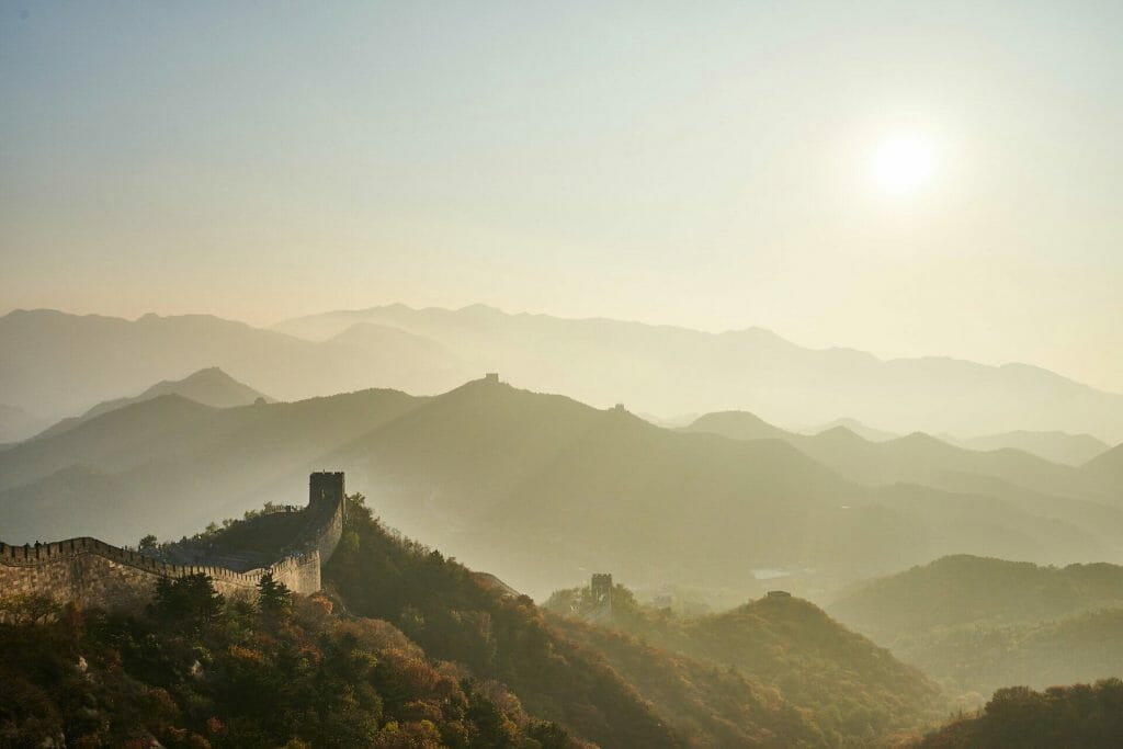 Great wall of China with sun in the sky and foggy haze