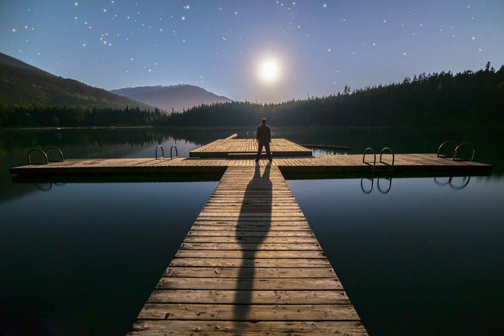 Person on a deck over water at night