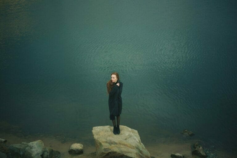 Life Sucks quotes woman alone at water wearing black